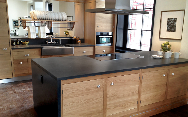 Custom black concrete kitchen island countertop and sink counter by Trueform.