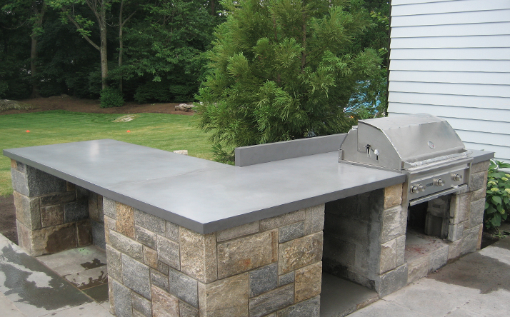 Outdoor custom kitchen wrap counter top with grill and stone base by Trueform Concrete.