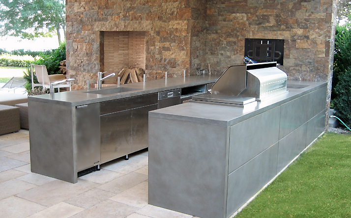 Double outdoor custom concrete counter tops with under mount sink and concrete wall panels by Trueform Concrete.