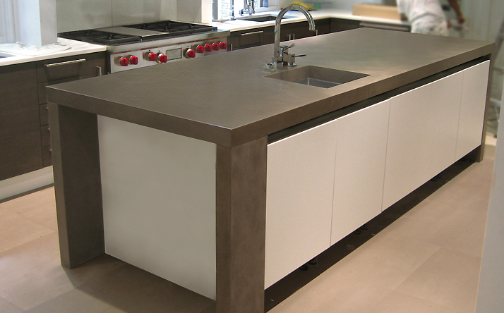 Large gray custom kitchen counter top with under mount sink. Trueform Concrete.