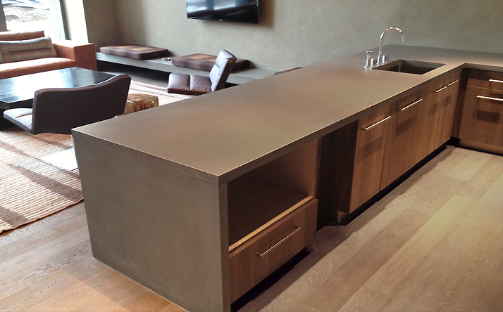 Light brown custom wrap concrete kitchen counter tops with under mount sink and waterfall leg by Trueform Concrete.