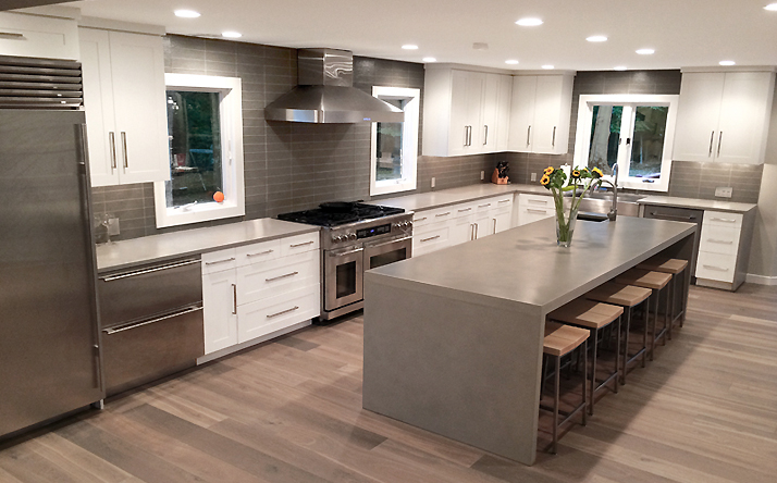 Custom gray concrete kitchen counter with double waterfall legs by Trueform Concrete.