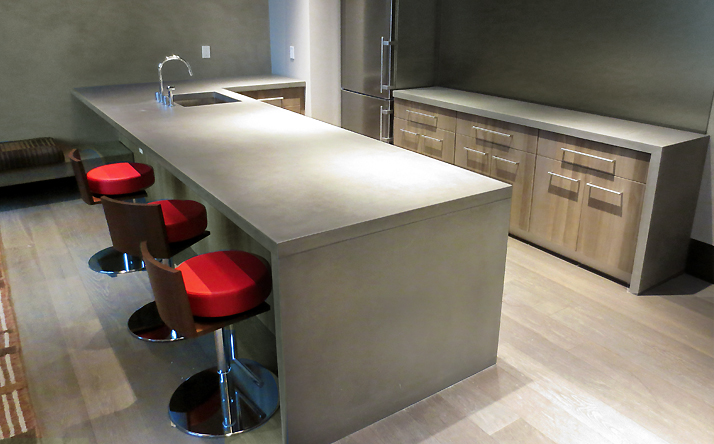 Gray custom concrete countertop with under mount sink with waterfall leg by Trueform Concrete.