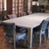 Long light gray custom concrete dining room table with wood base by Trueform Concrete.
