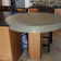 Custom light gray round pedestal kitchen table on an island by Trueform Concrete